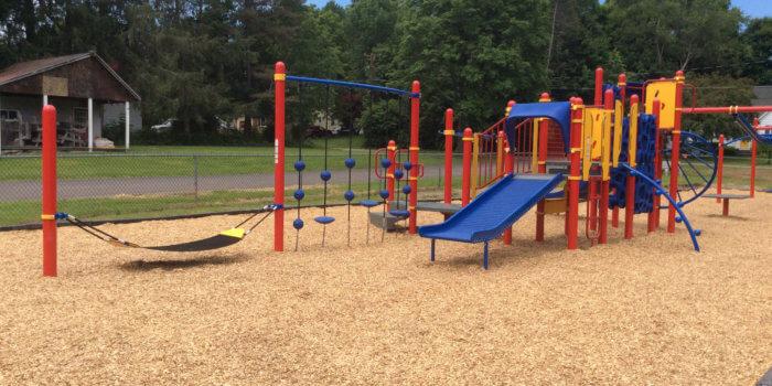Photo of playground with climbers, slides, and zipline.