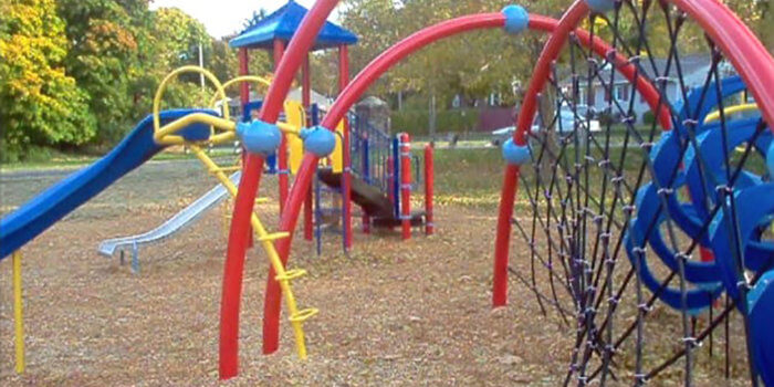 Photo of playground with slides, climbers, and climbing nets.