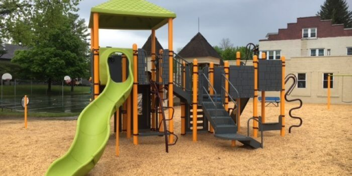 Photo of a play structure with a roof, slide, and multiple climbers and panels.