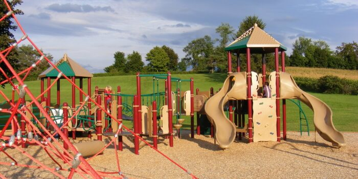 Photo of playground with slides, climbers, and a rope climbing structure.