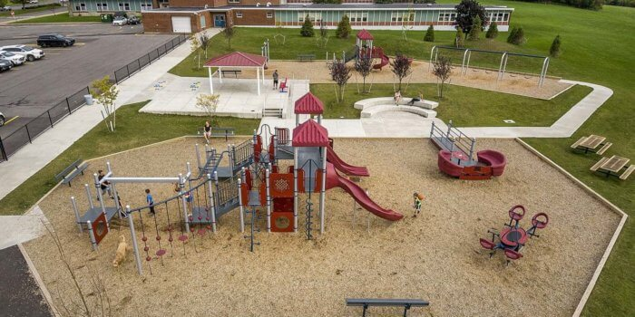 Photo of expansive play area with two separate playground structures, multiple independent components, and a pavilion