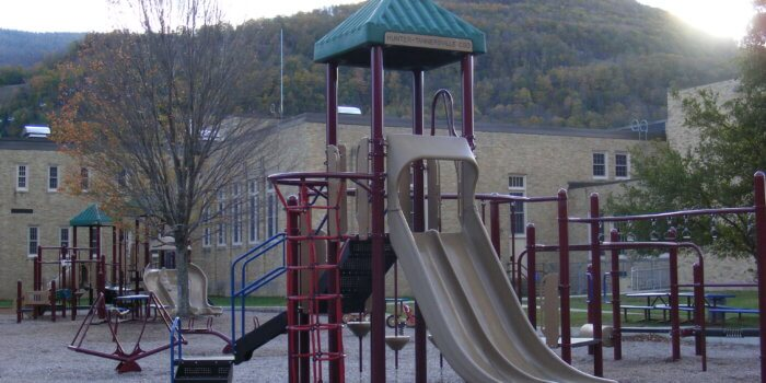 Photo of playground with multiple play structures as well as independent components.