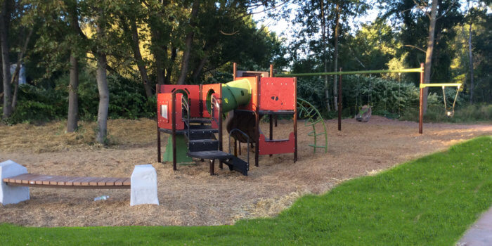 Photo of playground with swings, slides, climbers, and tunnels.