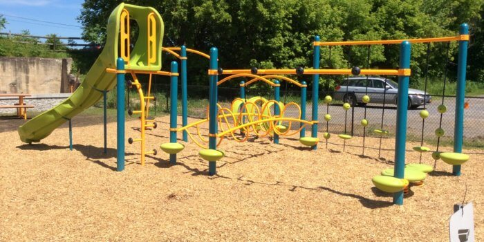 Photo of a play structure with slide and numerous climbing components