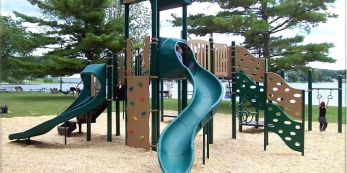 Photo of playground with climbers, slides, and climbing walls on a lake shore.