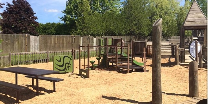 Photo of playground with climbers, slide, and play panels.