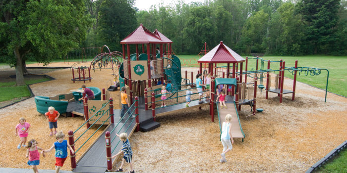 Photo of children playing on a large play structure with several ramps, decks, and roofs, and many climbers and slides