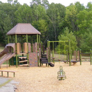 Photo of a play structure with multiple slides and climbers, swings, and independent components