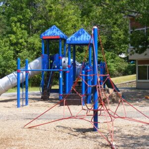 Photo of a climbing net structure with a large play structure, with attached slides and climbers, in the background
