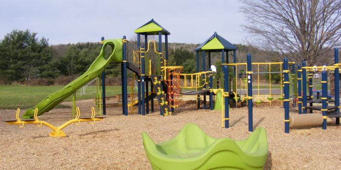 Photo of large play structures with slides, nets, and climbers, and a large spinner in front