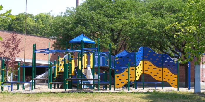 Photo of a large play structure with climbing walls, slides, and overhead climbers