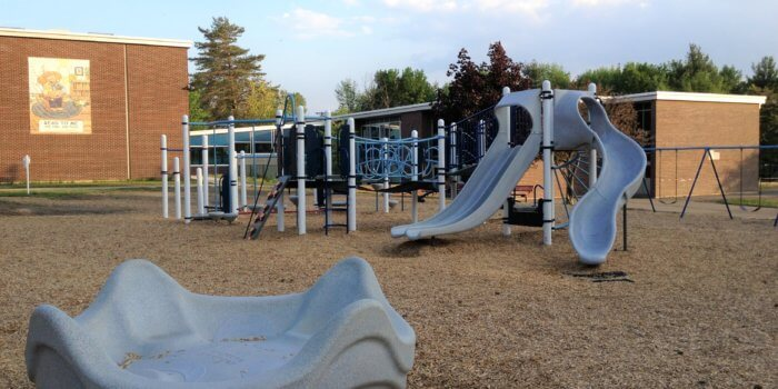 Photo of a play structure with multiple slides and climbers, as well as a large independent spinner