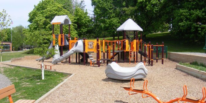Photo of a play structure with multiple slides, climbers, and decks, and a large independent spinner