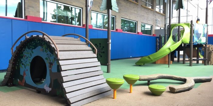 Photo of custom, nature-inspired play components featuring trees, logs, and wild animals, inside the enclosed courtyard