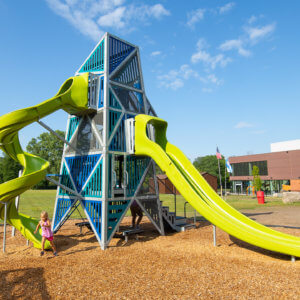 Photo of a tall geometric play tower with two winding slides