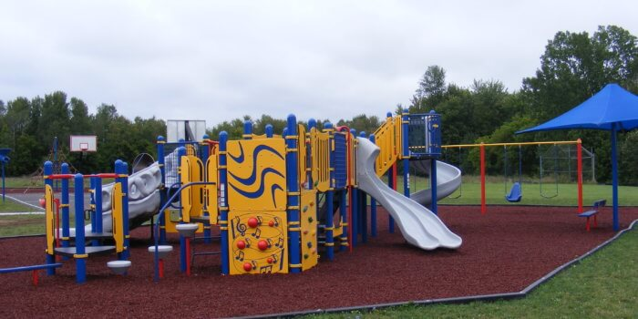 Photo of a playground with climbers, slides, and swings.