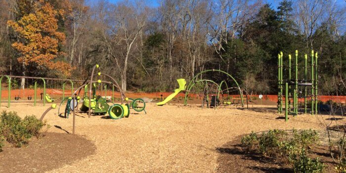 Photo of playground with climbing net structure, swings, slides, tunnels, and climbers.
