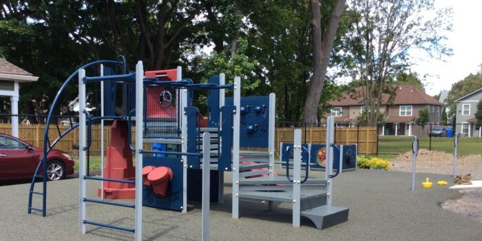 Photo of small play structure with climbers, a slide, and play panels