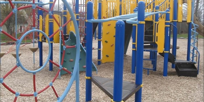 Photo of playground with climbers, slides, laders, and climbing structures.