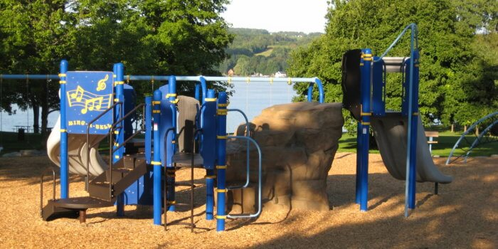 Photo of play structure with climbers, decks, slides, and rock structures overlooking a lake