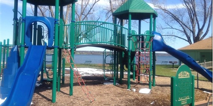 Photo of playground with climbers, slides, and bridge on the lakeside.