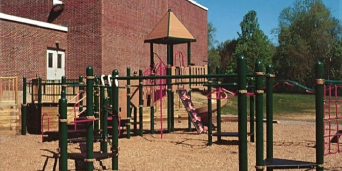 Photo of playground with climbers, slides, and overhead play components.