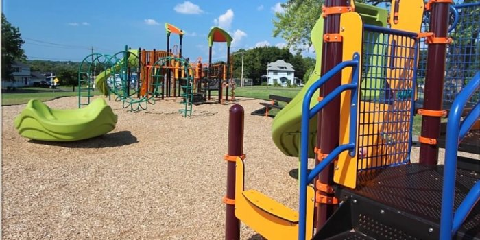 Photo of playground with climbing structures, slides, a spinner, and multiple levels of decks.