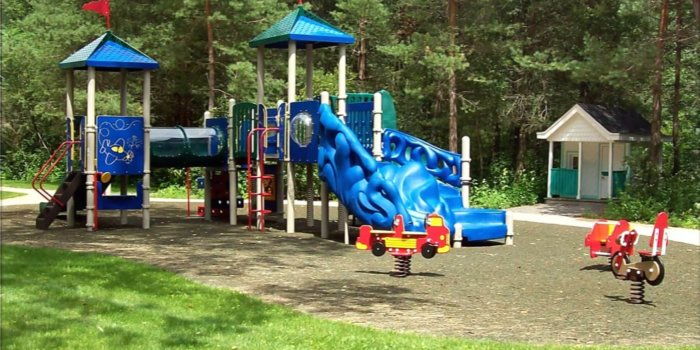 Photo of playground with slides, climbers, play panels, and spring riders.