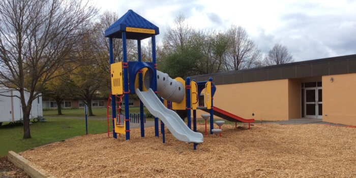 Photo of play structure with slides, climbers, and a tunnel bridge.