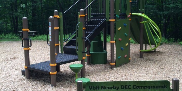 Photo of playground with climbers, a slide, and educational play panels.
