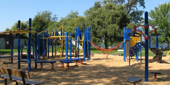 Photo of play equipment including multiple decks, climbers and overhead components connecting them, and slides