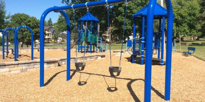 Photo of playground with swings, slides, covered decks, and climbers.