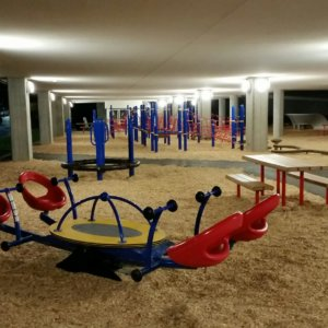 View of play equipment - a seesaw and climbing structures - illuminated beneath the school at night