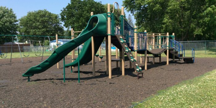 Photo of playground with slides, climbers, and bridge.