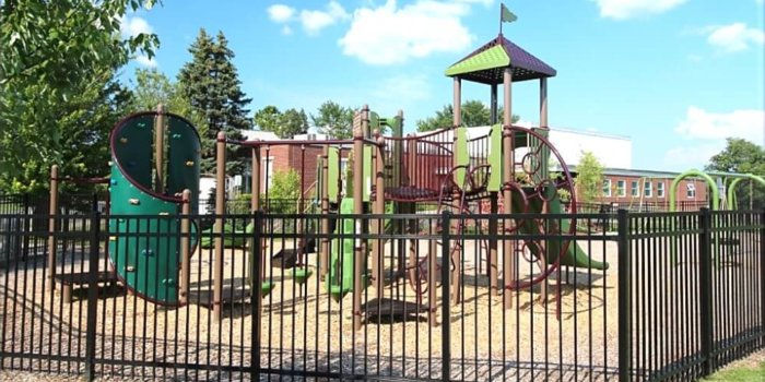 Photo of playground with slides, climbers, and swings surrounded by a fence.