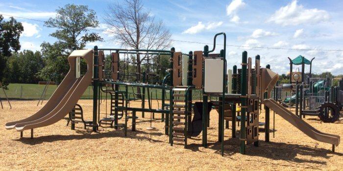 Photo of playground with slides, climbers, decks, and bridges.