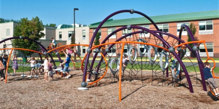 Photo of playground with curved climbing nets, ladders, and spinners.