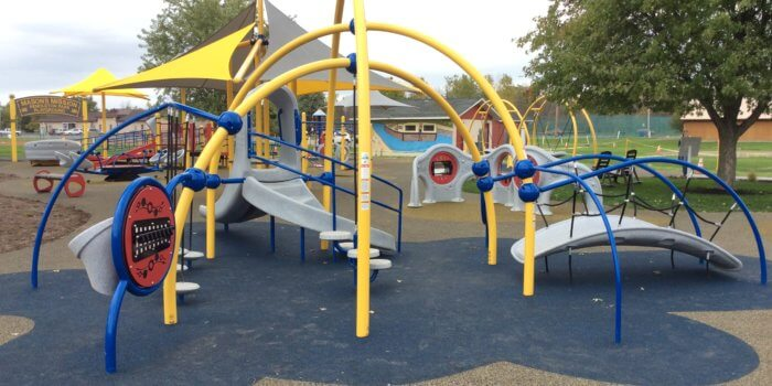 Photo of the completed playground, showing an arching play structure with num