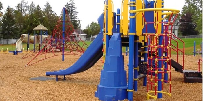 Photo of playground with climbers, slides, and rope climbing structure.