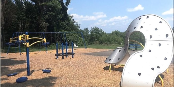 Photo of playground with swings, spinners, and climbing structure.