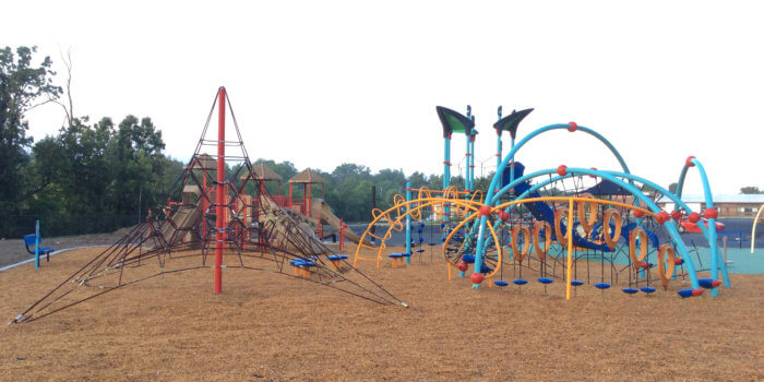 Photo of a large playground with multiple curved netted climbing structures, as well as play structures with slides, climbers, and decks.
