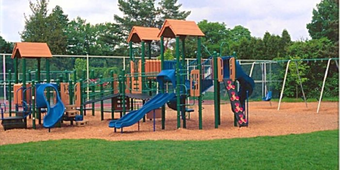 Photo of playground with climbers, slides, and swings