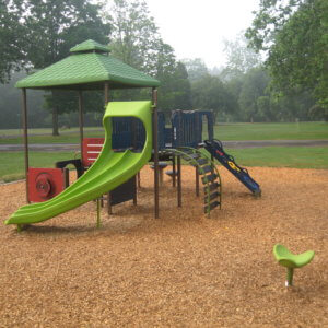 Photo of a play structure for 2-5 year olds, with climbers, a slide, and a spinner