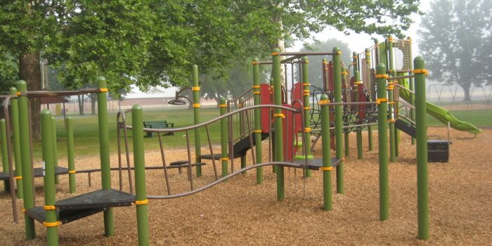 Photo of play equipment for ages 5-12, with multiple structures connected by climbing components