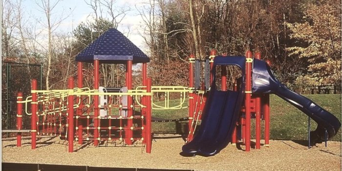 Photo of playground with climbers, slides, and climbing nets.