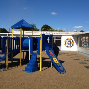 Photo of a playground in a schoolyard with slides, tunnels, and climbers.