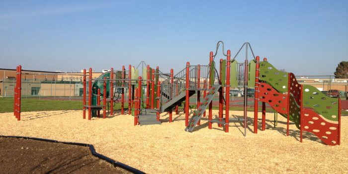 Photo of playground with climbing components, slides, and bridges.