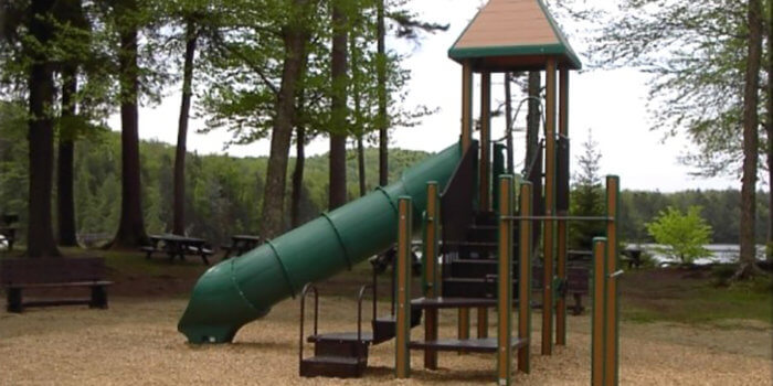 Photo of playground with climbers, slides, and peaked roof.