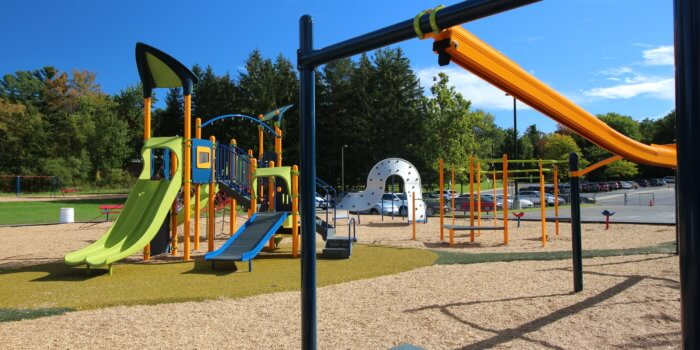 Photo of playground with zipline, spinners, and a play structure with several slides and climbers.