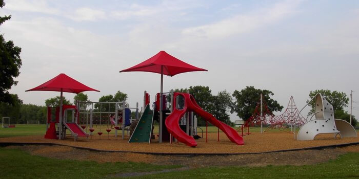 Photo of playground with multiple play and climbing structures and shades.